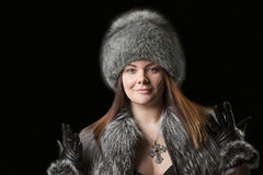Fur hat. Portrait of a beautiful young woman in a fur hat, cape and leather gloves Royalty Free Stock Images