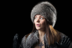 Fur hat. Portrait of a beautiful young woman in a fur hat, cape and leather gloves Stock Image