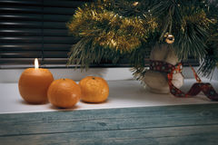 Fur tree branch with christmas decorations next to burning candle and tangerines on window sill Royalty Free Stock Photo