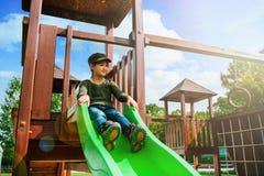 Furchtloses kleines Mädchen, das auf Spielplatz allein im sonnigen Wetter schiebt Lizenzfreies Stockfoto