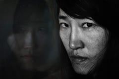 Furchtsam von Frau ` s Reflexion auf dem Spiegel, der zur Frau schaut Stockfotografie