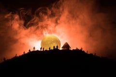 Furchtsame Ansichtmenge von Zombies auf Hügel mit gespenstischem bewölktem Himmel mit Nebel und steigendem Vollmond Schattenbildg Stockfotografie
