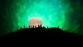 Furchtsame Ansichtmenge von Zombies auf Hügel mit gespenstischem bewölktem Himmel mit Nebel und steigendem Vollmond Schattenbildg Stockbild