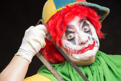 Furchtsame Clownspassvogel mit einem Lächeln und einem roten Haar mit einer Säge auf einem blac Stockbild