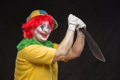 Furchtsame Clownspassvogel mit einem Lächeln und einem roten Haar mit einem großen Messer an Lizenzfreie Stockfotos