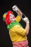 Furchtsame Clownspassvogel mit einem Lächeln und einem roten Haar mit einer Säge auf einem blac Lizenzfreie Stockbilder