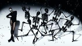 Furchtsame Frau mit dem Tanzen von schwarzen Skeletten Stockfoto