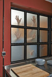 Furchtsame Hände auf Küchenfenster Stockbild