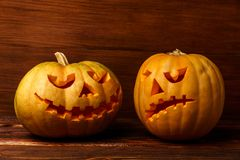 Furchtsame Halloween-Kürbise auf hölzernem Hintergrund Furchtsame glühende Gesichter Süßes sonst gibt's Saures Konzept von Hallow Lizenzfreie Stockbilder