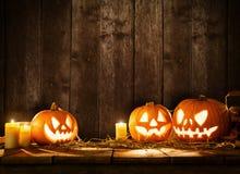 Furchtsame Halloween-Kürbise auf hölzernen Planken Lizenzfreie Stockfotografie
