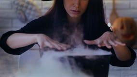Furchtsame Hexe, die Zaubertränke in ihrem Topf mit weißem Rauche, Halloween-Vorabend macht stock footage