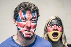 Furchtsame Paare mit britischer und deutscher Flagge auf Gesicht Stockfotografie