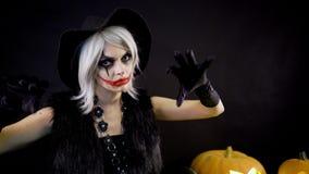 Furchtsame schöne Mädchenhexe feiert Halloween mit lustigen glühenden brennenden Kürbisen im Rauche Weibliche Zauberin mit Grau stock video