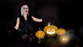 Furchtsame schöne Mädchenhexe lacht, verhöhnt, weidet sich, feiert Halloween mit lustigen glühenden brennenden Kürbisen im Rauche stock video footage