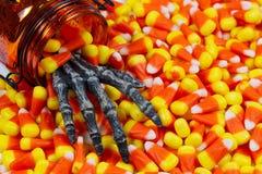 Furchtsame Skeletthand, die heraus Glas in einen Stapel von Süßigkeitsmais kommt Lizenzfreie Stockfotos
