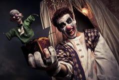 Furchtsamer Clown, der ein Jack-in-the-boxspielzeug anhält Stockfoto