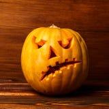 Furchtsamer Halloween-Kürbis auf hölzernem Hintergrund Furchtsames glühendes Gesicht Süßes sonst gibt's Saures Konzept von Hallow lizenzfreies stockbild
