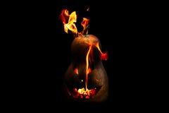 Furchtsamer Halloween-Kürbis spuckt die Feuerflamme, die auf Schwarzem lokalisiert wird Stockfotografie