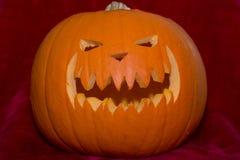 Furchtsamer Halloween-Kürbiskopf auf Rot Lizenzfreies Stockfoto