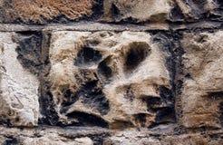 Furchtsamer Schädel in einer Steinwand Stockfoto