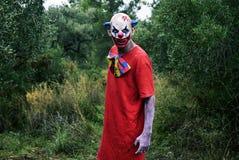 Furchtsamer schlechter Clown im Wald lizenzfreie stockfotografie
