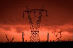 Furchtsamer Sonnenuntergang, mit rotem Himmel und Wolken, nach Sturm Treiben Sie Masten und industrielle Zäune in verheerender La lizenzfreie stockfotografie
