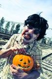 Furchtsamer Zombie mit einem geschnitzten Kürbis, mit einem Filtereffekt Stockbilder