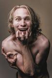Furchtsames Gelächter des verrückten nackten blonden Mannes Stockfotos