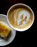 Furchtsames Gesicht auf schaumigem Kaffee Stockfoto