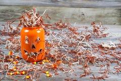 Furchtsames großes orange Kürbisglas auf rustikalem Holz Lizenzfreie Stockfotografie