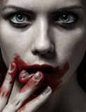 Furchtsames Mädchen- und Halloween-Thema: Porträt eines verrückten Mädchens mit einem blutigen Gesicht im Studio Stockfotos