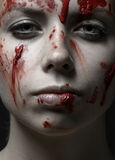 Furchtsames Mädchen- und Halloween-Thema: Porträt eines verrückten Mädchens mit einem blutigen Gesicht im Studio stockfoto