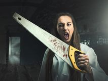 Furchtsames Porträt einer verärgerten Frau mit einer Säge Lizenzfreie Stockfotos