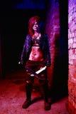 Furchtsames Porträt einer verärgerten Wahnsinnigefrau mit zwei machetas im Blut in Halloween-Art Stockfotos