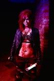 Furchtsames Porträt einer verärgerten Wahnsinnigefrau mit zwei machetas im Blut in Halloween-Art Stockbild