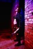Furchtsames Porträt einer verärgerten Wahnsinnigefrau mit zwei machetas im Blut in Halloween-Art Lizenzfreies Stockfoto