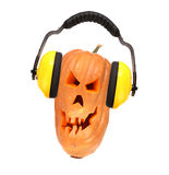 Furchtsames schlechtes Gesicht des Kürbises mit Kopfhörern. Lizenzfreie Stockfotografie