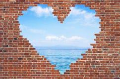 Fure o coração dentro da parede de tijolo, símbolo da forma do amor, parede de tijolo h Imagem de Stock