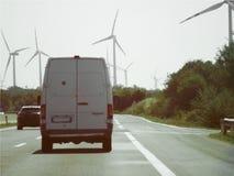 Furgone bianco su una strada vicino ad un parco eolico, grandi pali del vento che producono l'elettricità rinnovabile fotografia stock libera da diritti