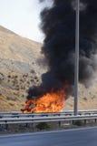 Furgoneta ardiente en la carretera Fotografía de archivo