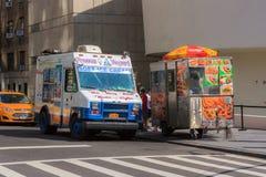 Furgoneta del helado y carro blancos y azules del perrito caliente en una calle en nuevo foto de archivo libre de regalías