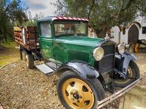 Furgoneta verde clásica del taller con las participaciones de madera parqueadas en casa colonial vieja fotografía de archivo