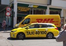 Furgoneta y taxi de DHL en la calle Foto de archivo libre de regalías