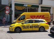 Furgoneta y taxi de DHL en la calle Fotografía de archivo libre de regalías