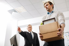 Furious aged employer firing the employee from the company royalty free stock images