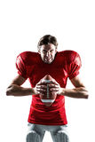 Furious American football player in red jersey holding ball Stock Photos