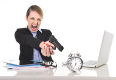 Furious angry businesswoman working pointing gun to alarm clock in out of time concept. Young attractive businesswoman furious and angry working with computer Royalty Free Stock Photo