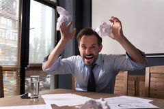Furious angry man losing his temper. Nervous breakdown. Hysterical frantic angry man throwing crumpled paper around and grimacing while threatening you Stock Photography