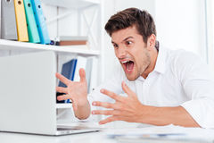Furious angry young businessman working with computer and shouting Royalty Free Stock Photo