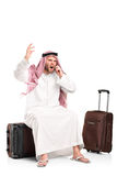 Furious arab shouting on a mobile phone. A furious arab shouting on a mobile phone seated on his luggage isolated on white background Stock Photos